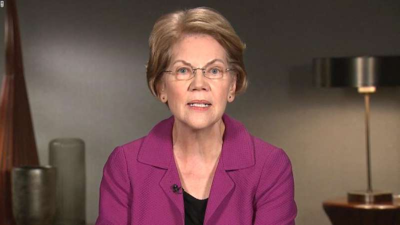 Elizabeth Warren wearing a purple shirt and smiling at the camera