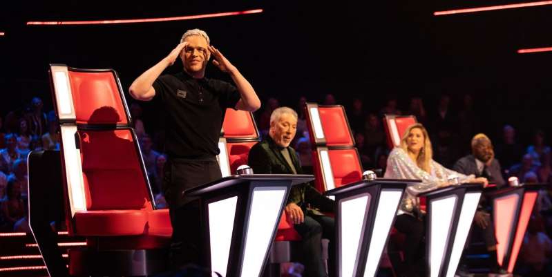 Tom Jones sitting in a chair: The Voice UK 2020's Olly Murs was left stunned by one auditionee in particular tonight (January 4), as his childhood friend and former co-worker Lara George auditions for the show.