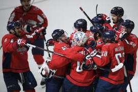 a group of baseball players standing on top of each other: Washington Capitals defenseman John Carlson (74), goaltender Braden Holtby (70), left wing Carl Hagelin (62), left wing Alex Ovechkin (8), of Russia, and others celebrate after an NHL hockey game against the San Jose Sharks, Sunday, Jan. 5, 2020, in Washington. (AP Photo/Nick Wass)