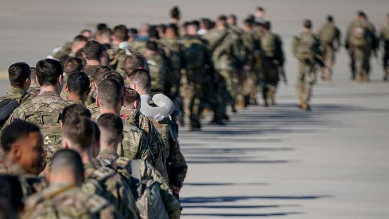 a group of people standing in front of a crowd: American troops deploying to the Middle East from Fort Bragg in North Carolina on Sunday.
