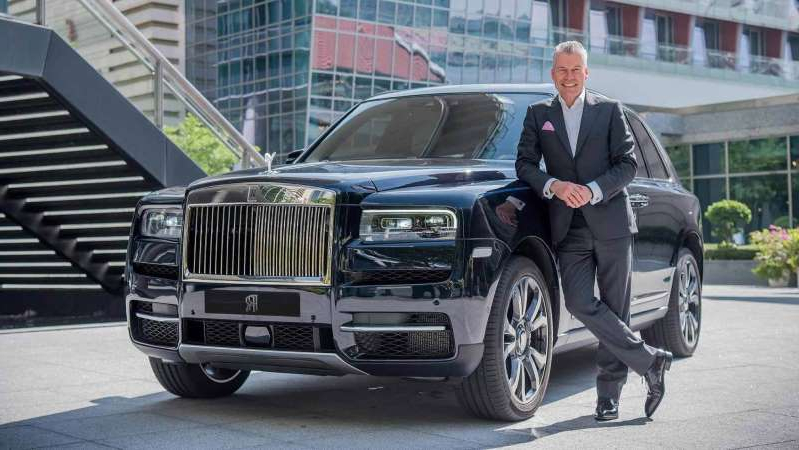 a man riding on the back of a car: Torsten Muller-Otvos, Chief Executive, Rolls-Royce Motor Cars