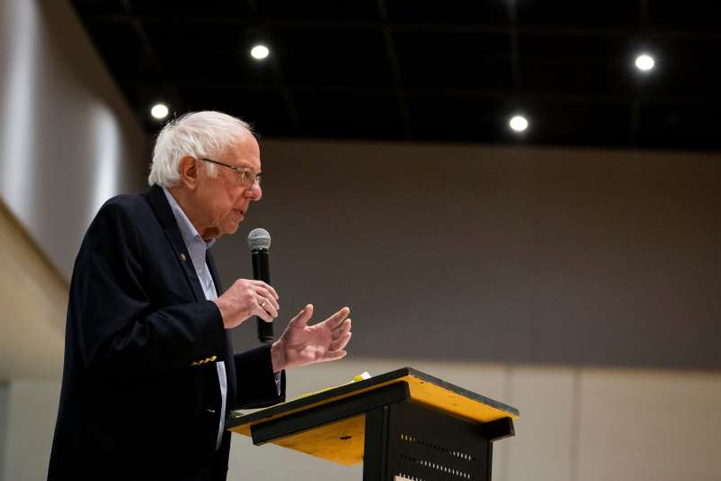 a man standing in front of a table: Vermont Senator and 2020 Democratic presidential candidate Bernie Sanders speaks at the Iowa Farmers Union Annual Convention at Hotel Grinnell on Friday, Dec. 6, 2019, in Grinnell.