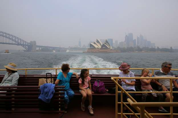 Slide 1 of 67: The Sydney Opera House and Sydney Harbour Bridge are seen through smoke haze from bushfires as passengers ride a ferry in Sydney on Jan. 8.