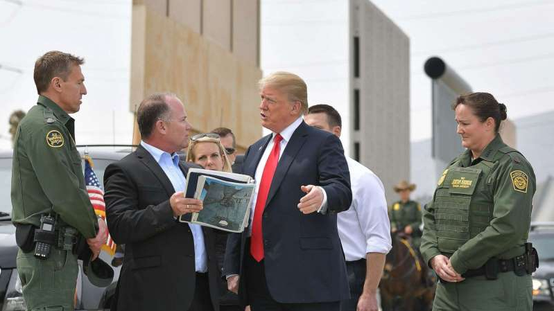 Donald Trump et al. standing next to a person in a suit and tie: President Donald Trump is shown border wall prototypes in San Diego, Calif., March 13, 2018.