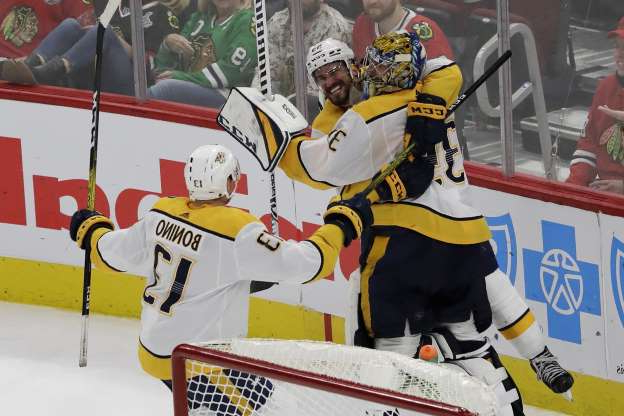 Nashville Predators goalie Pekka Rinne, left, celebrates with defenseman Roman Josi, center, and center Nick Bonino after scoring a goal against the Chicago Blackhawks during the third period of an NHL hockey game in Chicago, Thursday, Jan. 9, 2020. (AP Photo/Nam Y. Huh)