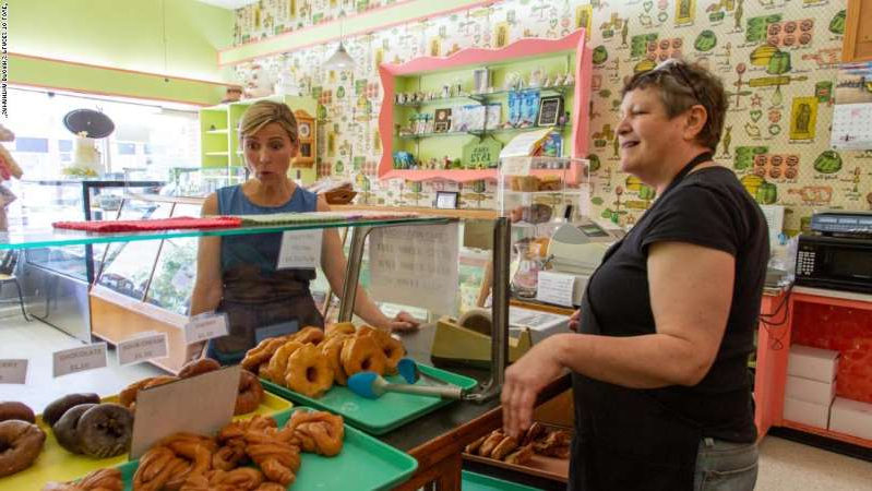 Samantha Brown preparing food while standing in front of a store: Brown got an introduction to