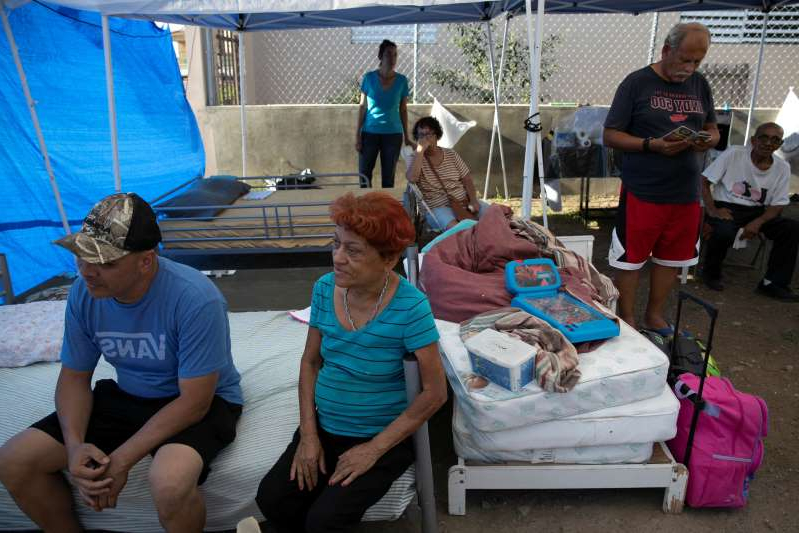 People rest at a camp set up in a lot next to their homes after the earthquake in Yauco, Puerto Rico, January 9, 2020. REUTERS/Marco Bello