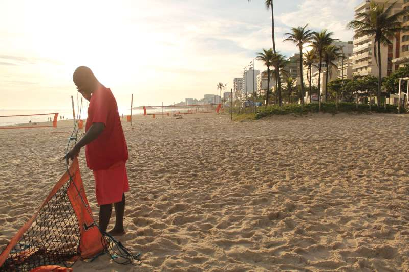 a person standing on a beach: Henrique de Rei sets up his kiosk on an empty beach before 6 a.m. on a recent morning.
