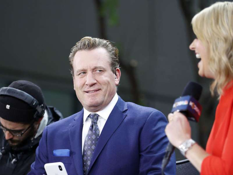 Jeremy Roenick wearing a suit and tie talking on a cell phone