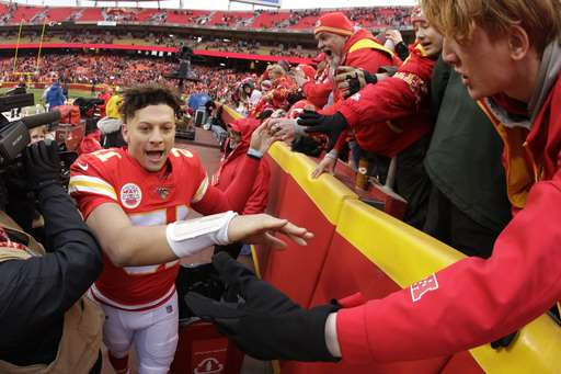 Patrick Mahomes et al. standing in front of a crowd: Kansas City Chiefs quarterback Patrick Mahomes (15) celebrates with fans after an NFL football game against the Los Angeles Chargers, Sunday, Dec. 29, 2019, in Kansas City, Mo. (AP Photo/Charlie Riedel)