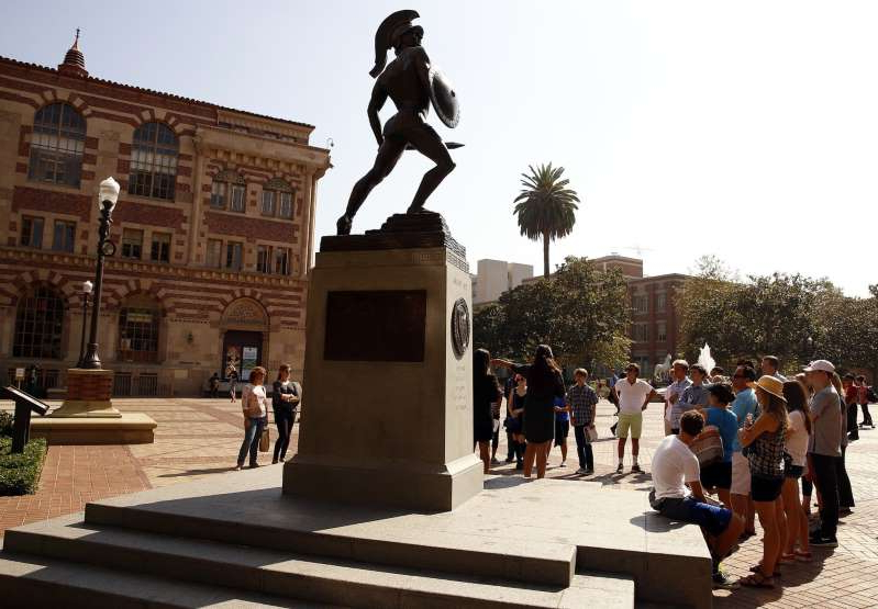 a group of people walking in front of a statue of a man: An Asian undergraduate student at USC has reported that someone threw eggs at him and shouted racial slurs as he sat outside his campus residence early Sunday. Above is a file photo of the USC campus.