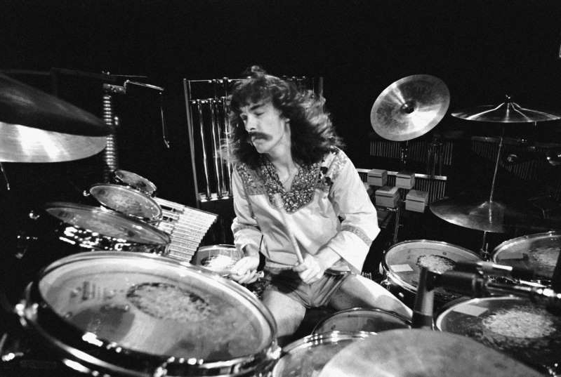 a person sitting on a pan: Drummer Neil Peart performs with Rush in 1978.