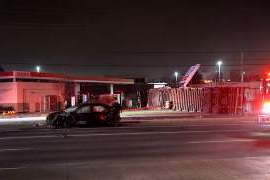 a traffic light sitting on the tarmac at night: A tractor trailer crashed into an Esso gas station sign on Eglinton Avenue West in Mississauga early Monday.