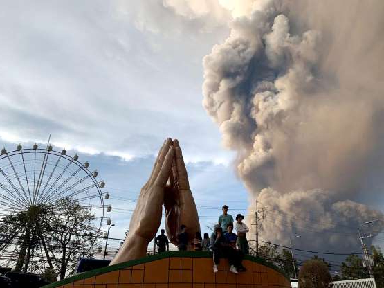 Slide 1 of 11: People watch as the Taal volcano spews ash and smoke during an eruption in Tagaytay, Cavite province south of Manila, Philippines on Sunday. Jan. 12, 2020.  A tiny volcano near the Philippine capital that draws many tourists for its picturesque setting in a lake belched steam, ash and rocks in a huge plume Sunday, prompting thousands of residents to flee and officials to temporarily suspend flights.