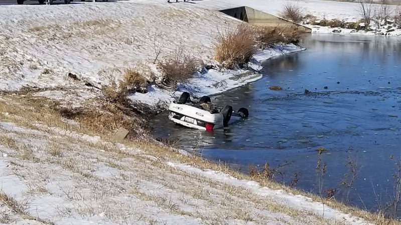 a body of water: A car sits overturned in an icy pond in Bellevue, Neb., on Jan. 11, 2020.