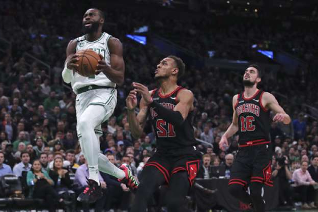 a group of basketball players on the field: Boston Celtics guard Jaylen Brown (7) outruns Chicago Bulls guard Tomas Satoransky (31) and forward Daniel Gafford (12) on a drive to the basket during the first half of an NBA basketball game in Boston, Monday, Jan. 13, 2020. (AP Photo/Charles Krupa)