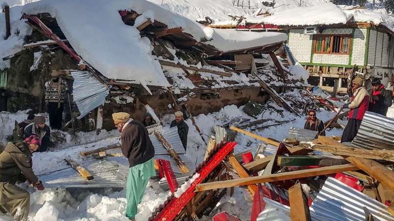 a group of people sitting in the snow: Workers clear the destruction in the path of the avalanches
