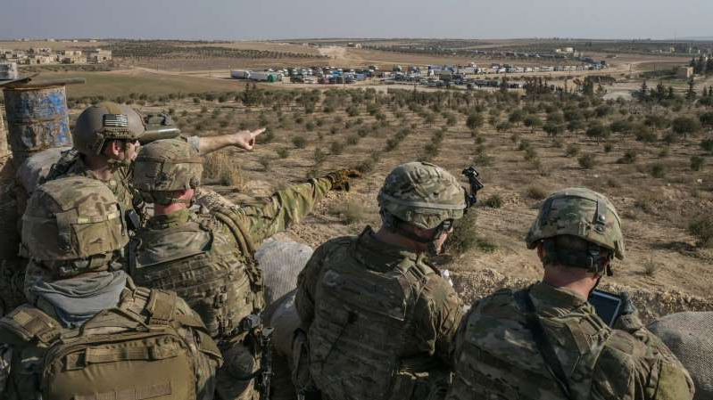 a group of people wearing military uniforms: American Special Forces troops at an outpost outside the town of Manbij in northern Syria in 2018.