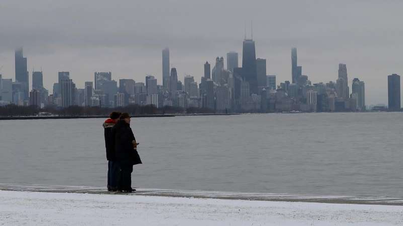 a person standing in a body of water with a city in the background: Adam Klotz has your FoxCast.
