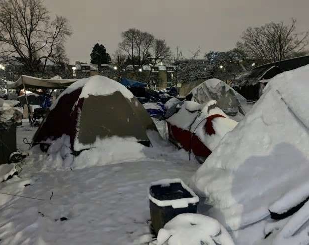 a pile of snow: Snow drifts between dozens of tents at Oppenheimer Park around dawn at Vancouver on Jan. 13, 2020.