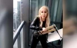 a woman standing in front of a mirror posing for the camera: A video appears to show a woman throwing a chair off a balcony in Toronto.