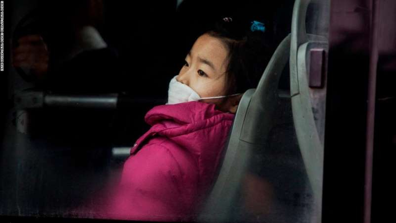 BEIJING, CHINA - DECEMBER 08:  A Chinese girl wears a mask to protect against pollution as she rides a bus in heavy smog on December 8, 2015 in Beijing, China. The Beijing government issued a