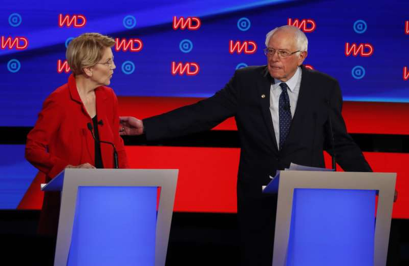 Bernie Sanders et al. standing in front of a computer screen: Sen. Bernie Sanders, I-Vt., gestures toward Sen. Elizabeth Warren, D-Mass., during the first of two Democratic presidential primary debates hosted by CNN Tuesday, July 30, 2019, in the Fox Theatre in Detroit. (AP Photo/Paul Sancya)