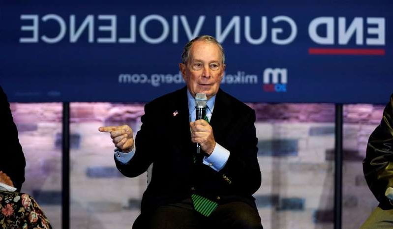 Michael Bloomberg holding a sign: Michael Bloomberg speaks about his gun policy agenda in Aurora, Colo., December 5, 2019.