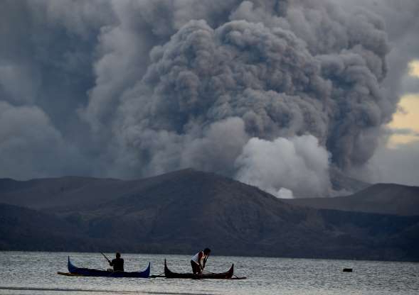 Slide 1 of 27: Residents living along Taal lake catch fish as Taal volcano erupts in Tanauan town, Batangas province south of Manila on January 14, 2020. - Taal volcano in the Philippines could spew lava and ash for weeks, authorities warned on January 14, leaving thousands in limbo after fleeing their homes fearing a massive eruption.