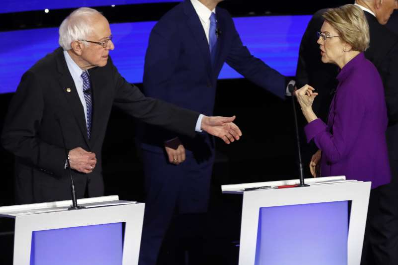 a group of people standing next to a person in a suit and tie: Democratic presidential candidate Elizabeth Warren appears to refuse Bernie Sanders' outstretched hand at the conclusion of the final Democratic debate (Patrick Semansky/AP)
