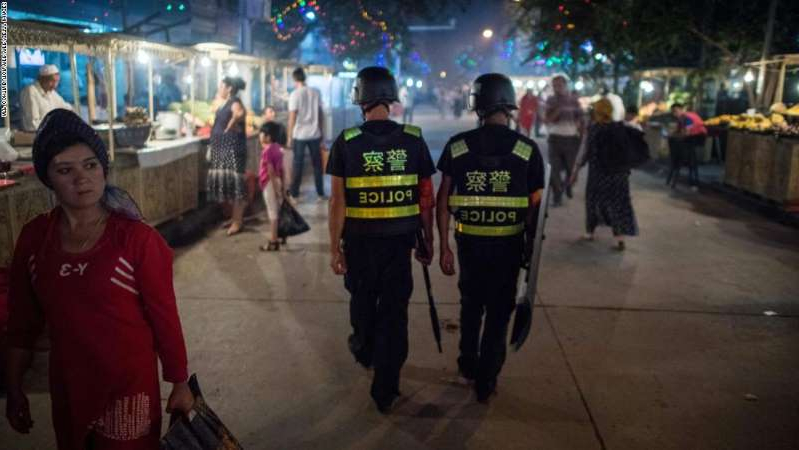 a group of people standing on a sidewalk: This picture taken on June 25, 2017 shows police patrolling in a night food market near the Id Kah Mosque in Kashgar in China's Xinjiang Uighur Autonomous Region, a day before the Eid al-Fitr holiday. The increasingly strict curbs imposed on the mostly Muslim Uighur population have stifled life in the tense Xinjiang region, where beards are partially banned and no one is allowed to pray in public. Beijing says the restrictions and heavy police presence seek to control the spread of Islamic extremism and separatist movements, but analysts warn that Xinjiang is becoming an open air prison. / AFP PHOTO / Johannes EISELE / TO GO WITH China-religion-politics, FOCUS by Ben Dooley        (Photo credit should read JOHANNES EISELE/AFP/Getty Images)