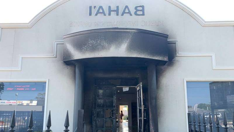a living area with a building in the background: Damage to the Baha'i Centre at North Brighton from a deliberately-lit fire. (ABC News: Isadora Bogle)