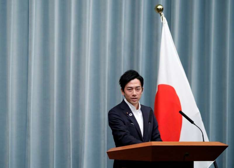 Shinjiro Koizumi wearing a suit and tie in front of a curtain: Japan's Environment Minister Koizumi attends a news conference at PM Abe's official residence in Tokyo