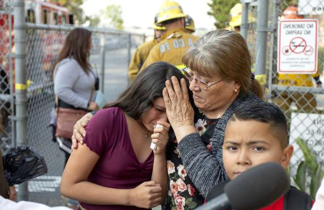 Slide 1 of 12: Grandmother Teresa Santoya, left, consoles student Marianna Torres, 11, center, as she evacuates Park Avenue Elementary School after jet fuel fell on the school in Cudahy, Calif., Tuesday, Jan. 14, 2020. Jet fuel dumped by an aircraft returning to Los Angeles International Airport fell onto the school playground where children were playing Tuesday, fire officials said. The Los Angeles County Fire Department said firefighters assessed over a dozen children and several adults who complained of minor injuries and none needed to be taken to a hospital. (AP Photo/Damian Dovarganes)