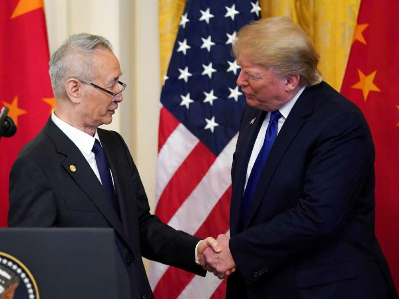 a couple of people standing next to a person in a suit and tie: U.S. President Donald Trump with Chinese Vice Premier Liu He during a signing ceremony for Phase 1 of the U.S.-China trade agreement in the White House, Jan. 15, 2020.