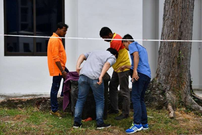 a group of people standing in the grass: FILE PHOTO: Police officers and cleaners inspect the contents of a bin at a rubbish chute, after a baby was found alive among rubbish in the bin at a public housing estate in Singapore