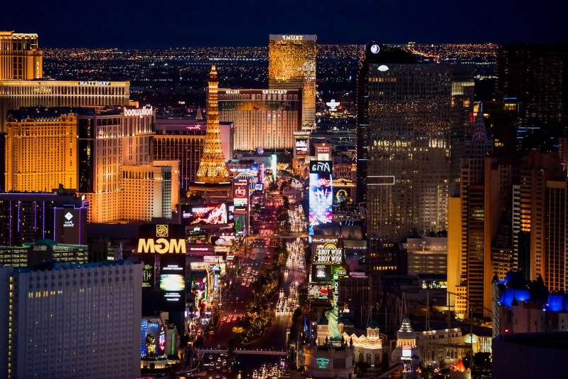 a lit up city at night with Las Vegas Strip in the background: Hotels stand on The Strip in this aerial photograph taken at dusk above Las Vegas, Nevada, U.S., on Wednesday, Aug. 5, 2015.