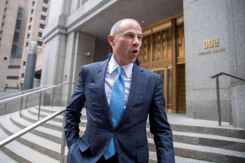a man wearing a suit and tie standing in front of a building: Michael Avenatti is due in court on Jan. 21, but that is now in jeopardy after his arrest in California. (AP)