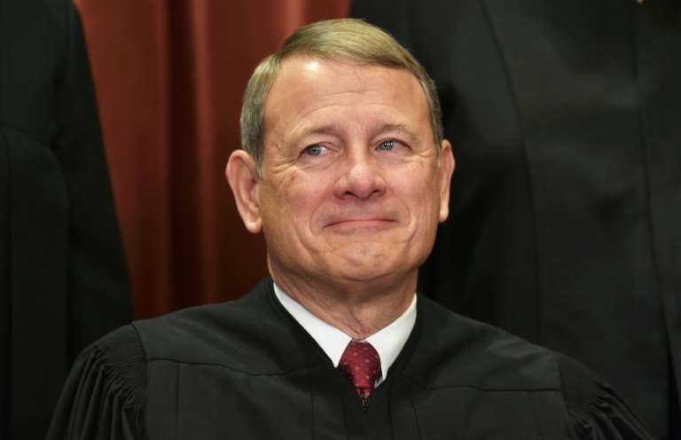 John Roberts wearing a suit and tie smiling at the camera: US Supreme Court Chief Justice John Roberts