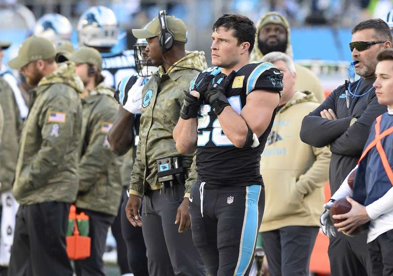 Luke Kuechly et al. in uniform standing in front of a crowd: Carolina Panthers middle linebacker Luke Kuechly (59) watches from the sidelines against the Atlanta Falcons at Bank of America Stadium in Charlotte, N.C., on November 17, 2019.
