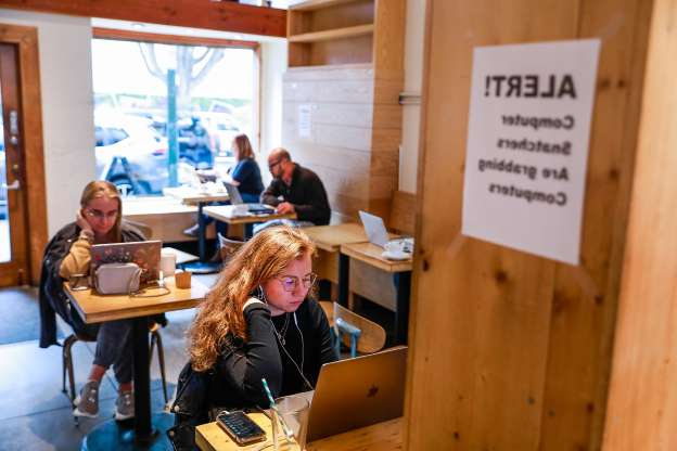 Slide 1 of 5: (L-r) Sofya Freeman and Katya Yetmolaieva sit beside a sign alerting them to laptop theft as they work on their laptops at Haus coffee shop in the Mission on Wednesday, Jan. 15, 2020 in San Francisco, California. Haus coffee experienced laptop theft from their shop about 7 months ago.