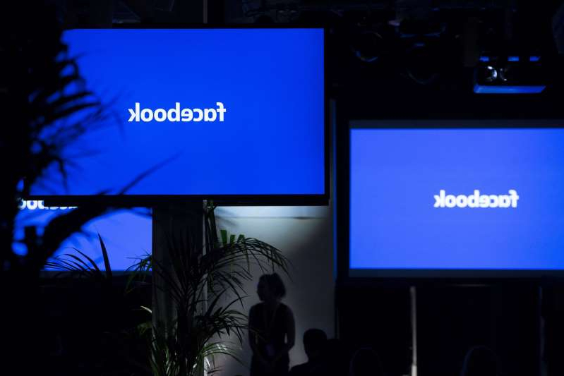 a flat screen television: The Facebook Inc. logo sits on screens ahead of the global launch event of