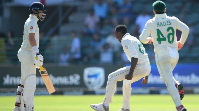 a group of baseball players standing on top of a field: Kagiso Rabada celebrates the wicket of Joe Root