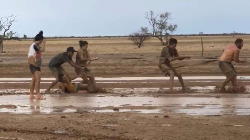 a group of people on a beach: People slide around in the mud, celebrating the rainfall in Winton, Queensland