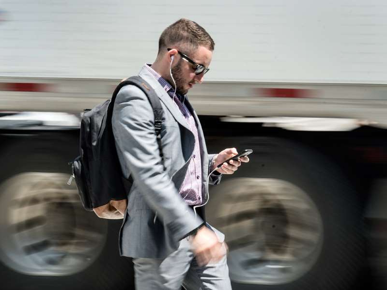 a man standing next to a car: A man using a cellphone in Toronto.
