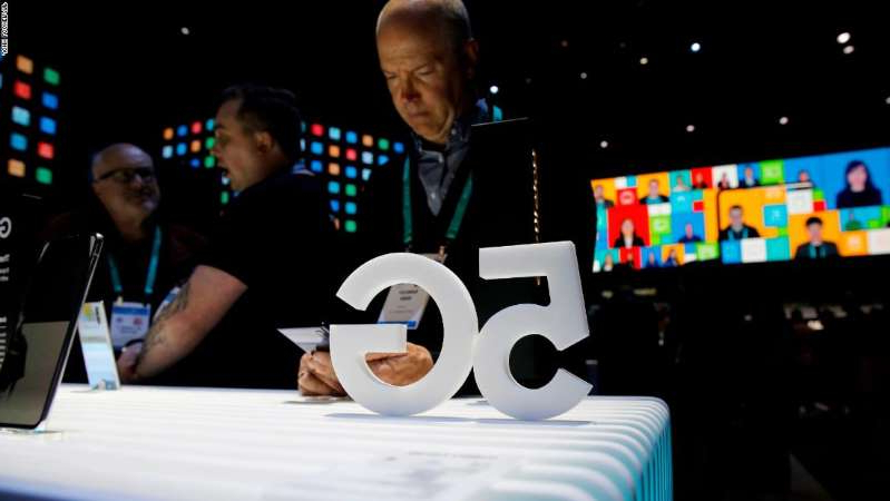 a person sitting at a table in front of a computer screen: People loook at 5G phones at the Samsung booth during the CES tech show, Tuesday, Jan. 7, 2020, in Las Vegas. (AP Photo/John Locher)