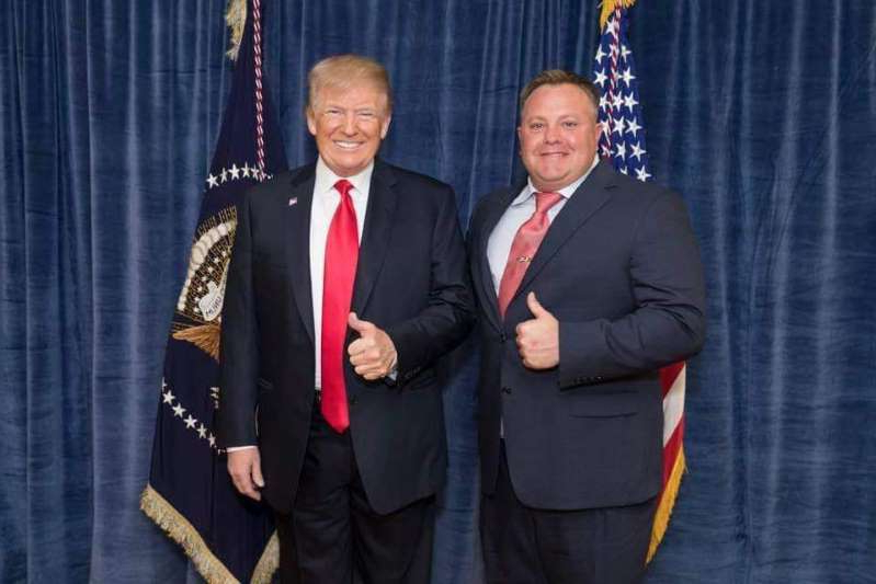 Donald Trump in a suit standing in front of a curtain: Robert F. Hyde with President Donald Trump.