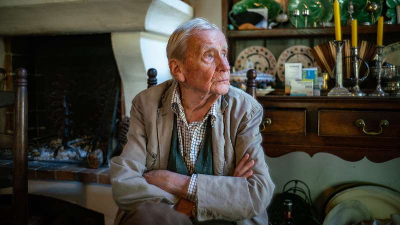 a person sitting on a table: Christopher Tolkien at his home in the South of France one week before his 95th birthday last year. For nearly 50 years after his father died in 1973, he worked to keep alive the world he had created.