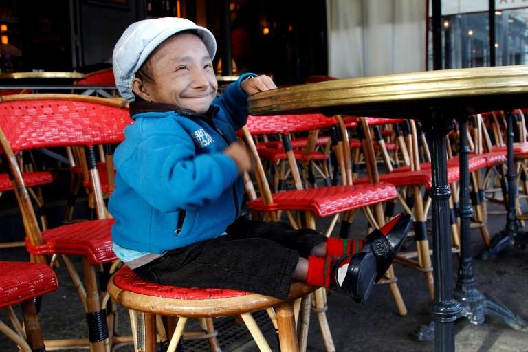 a small child sitting on a chair: Khagendra Thapa Magar is seen in a Paris cafe in October 2011