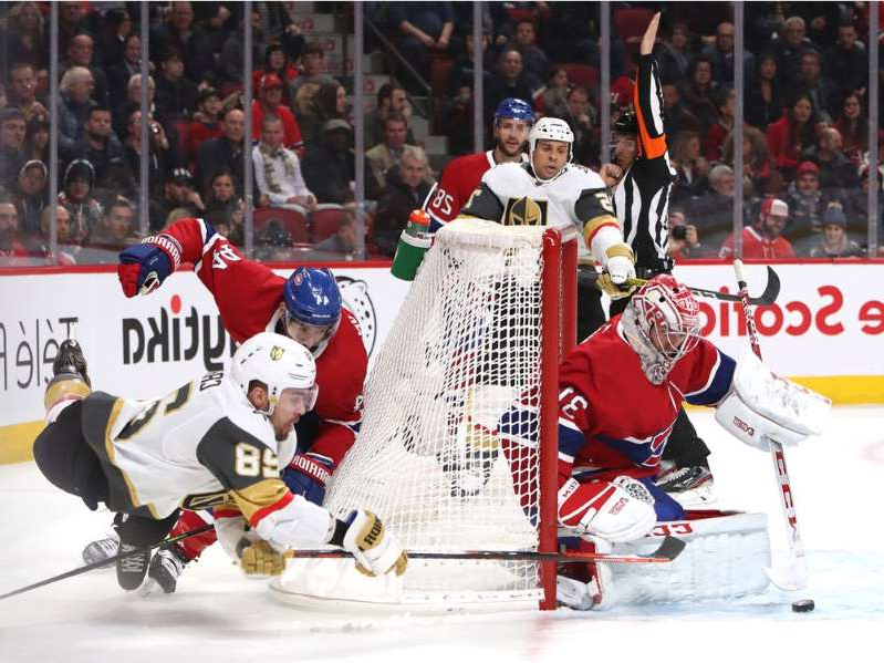 a group of hockey players on the snow:  Vegas Golden Knights' William Carrier (28) shoots the puck against Canadiens goaltender Carey Price as Nate Thompson (44) defends at Bell Centre in Montreal on Saturday, Jan. 18, 2020.